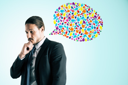 Attractive thoughtful young european businessman with creative colorful hand gesture speech bubble on blue background. Social network and communication concept Stockfoto