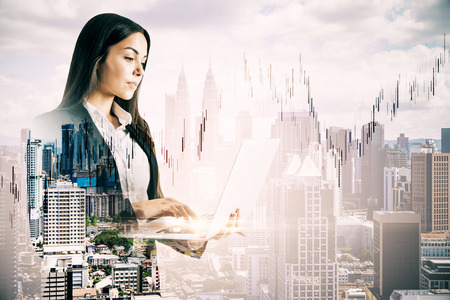 Side view of attractive young european businesswoman using laptop with forex chart on blurry city background. Communication and trade concept. Double exposure Stok Fotoğraf