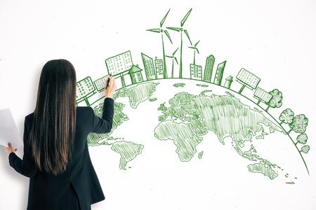 Businesswoman drawing creative eco globe croquis sur fond de mur blanc. Concept respectueux de l'environnement et de la pollution