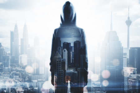 Hacker standing on blurry night city background with bokeh circles. Malware and phishing concept. Double exposure