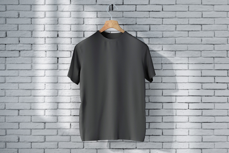 Hanger with empty black t-shirt hanging on brick wall background with sunlight. Shop print ad concept. Mock up, 3D Rendering