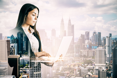 Pretty young businesswoman using laptop computer on blurry city background. Network and communication concept. Double exposure