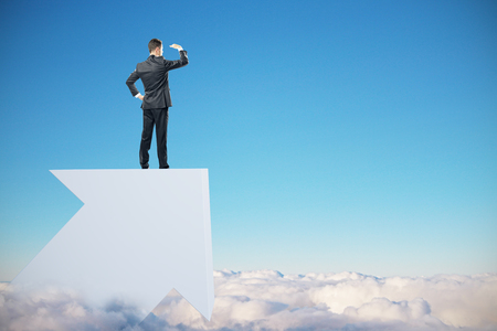 Businessman on cloudy sky background standing on white arrow and looking into the distance. Research and success concept