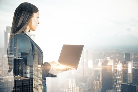 Joven empresaria con ordenador portátil en el fondo de la ciudad borrosa. Concepto de red y comunicación. Exposición doble Foto de archivo