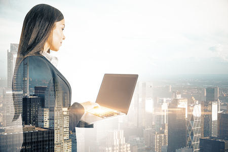 Young businesswoman using laptop computer on blurry city background. Network and communication concept. Double exposure Banco de Imagens