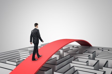 Businessman going over maze on red path. Challenge and overcome concept