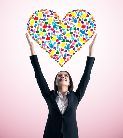 Young european businesswoman holding bright hand gesture heart on pink background. Community, care, donation, communication and hope concept Stockfoto