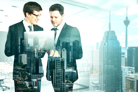 Attractive young european businessmen using laptop together on blurry office New York city interior background. Teamwork and network concept. Double exposure Stok Fotoğraf - 120797801