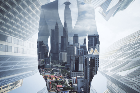 Unrecognizable businessman in suit standing on blurry city background. Career and success concept. Double exposure