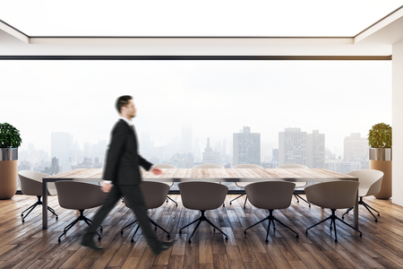 Side view of attractive young european businessman walking in modern meeting room with city view. Executive and boss concept.