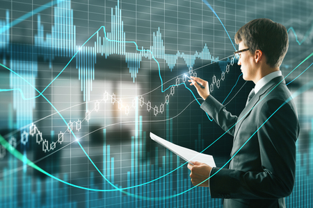 Attractive businessman with document in hand using creative forex chart interface on blurry office interior background. Finance and trade concept. Double exposure 写真素材