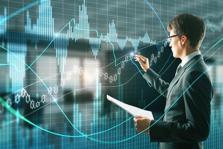 Homme d'affaires attrayant avec un document en main à l'aide d'une interface graphique forex créative sur fond intérieur de bureau flou. Concept financier et commercial. Double exposition Banque d'images
