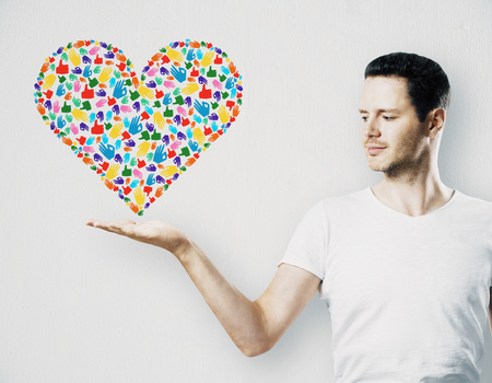 Attractive young guy holding creative hand gesture heart on white background. Community, care, donation, communication and hope concept