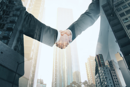 Side view of businessmen shaking hands together on bright city background. Teamwork and communication concept. Double exposure