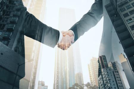 Vue latérale des hommes d'affaires se serrant la main sur fond de ville lumineuse. Concept de travail d'équipe et de communication. Double exposition