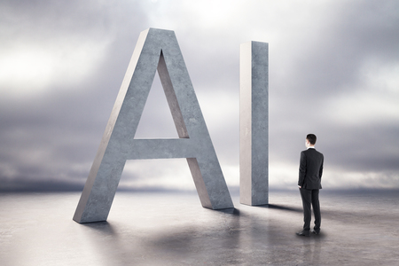 Businessman looking at creative concrete AI icon on cloudy background. Artificial intelligence and technology concept. Фото со стока