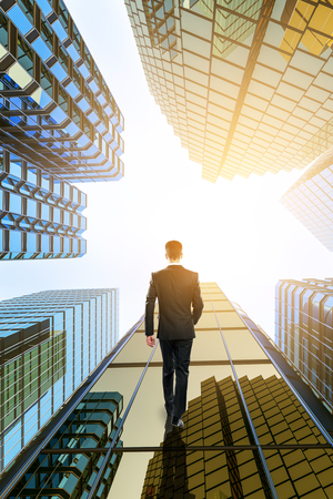 Bottom up view of businessman walking on glass skyscrapers in bright city. Downtown concept.