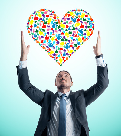 Young european businessman holding creative hand gesture heart on blue background. Community, care, donation, communication and hope concept
