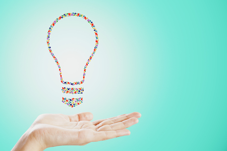 Held colorful hand gesture lightbulb on blue background. Communication, community, inspire, idea and innovation concept 스톡 콘텐츠