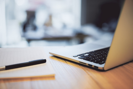 Side view and close up of laptop, notepad and pen on wooden desktop. Technology and workspace concept Stock Photo