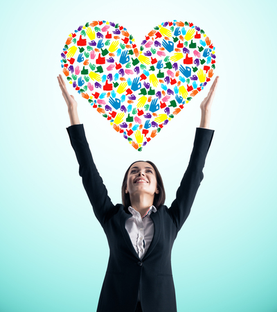 Young european businesswoman holding creative hand gesture heart on blue background. Community, care, donation, communication and hope concept Stockfoto