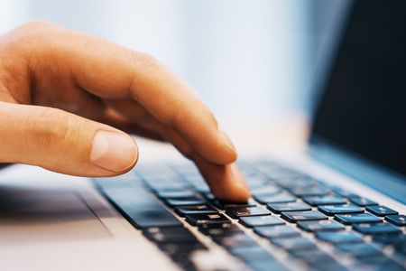 Side view of businessman hands using laptop keyboard on desktop workspace. Blurry background. Education, communication, programming and software concept