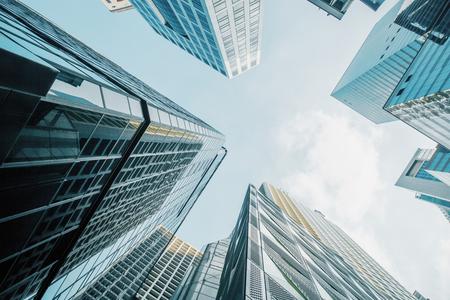 Ansicht von unten auf Wolkenkratzer auf strahlend blauem Himmelshintergrund. Urbanes und Lifestyle-Konzept