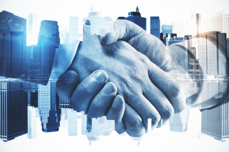 Side view of handshake on blurry city background. Teamwork and deal concept. Double exposure Stock Photo