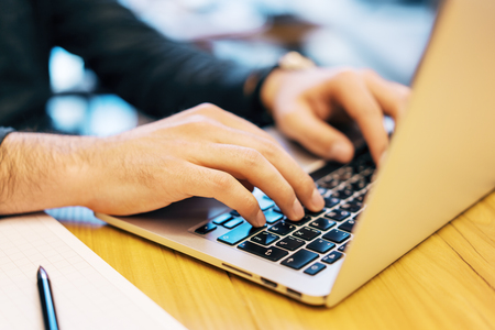 Side view of man hands using laptop keyboard while doing paperwork on wooden desktop and blurry background. Technology, programming and work concept