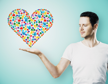 Attractive young guy holding colorful hand gesture heart on blue background. Community, care, donation, communication and hope concept Stockfoto