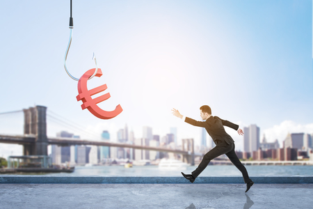 Businessman running after red euro sign on hook on beautiful bright city background. Invest and finance concept Stockfoto