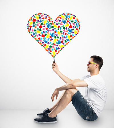Casual young man holding smartphone with creative hand gesture heart on white background. Community, care, donation, communication and hope concept