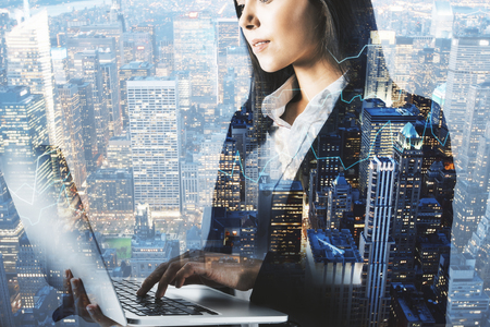 Side view of attractive young businesswoman using laptop on blurry night city background. Technology and network concept. Double exposure