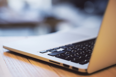 Close up of laptop keyboard on wooden desktop and blurry background. Technology and programming concept