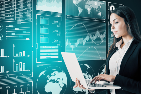 Attractive young businesswoman using laptop with abstract digital business interface on blurry background. Finance and innovation concept