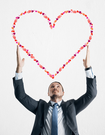 Young businessman holding creative hand gesture heart on white background. Community, charity and communication concept