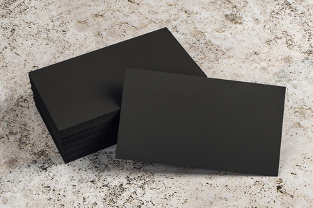Empty black business card stack on concrete desk. Info, address and message concept. Mock up, 3D Rendering