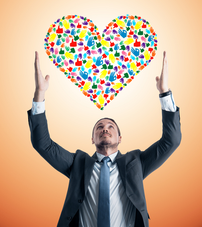 Young european businessman holding colorful hand gesture heart on orange background. Community, care, donation, communication and hope concept