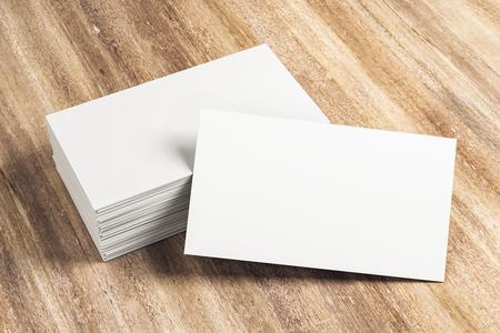 Leerer weißer Visitenkartenstapel auf hölzernem Schreibtisch. Info-, Adress- und Nachrichtenkonzept. Mock-up, 3D-Rendering Standard-Bild
