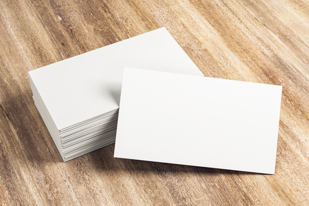 Blank white business card stack on wooden desk. Info, address and message concept. Mock up, 3D Rendering