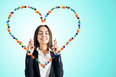 Young businesswoman with creative hand gesture heart on blue background. Community, donation and charity concept Archivio Fotografico - 121551828