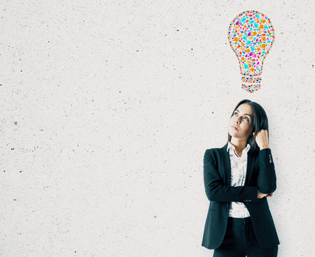 Portrait of pretty young european businesswoman with creative hand gesture lightbulb on concrete wall background. Communication, community, inspire, idea and innovation concept