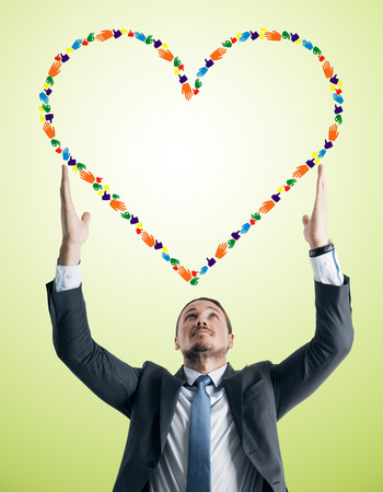 Young businessman holding creative hand gesture heart on green background. Community, charity and communication concept Stockfoto
