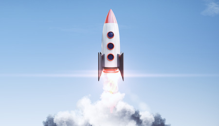 Creative launching rocket on bright blue sky with clouds background. Start up and exploration concept. 3D Rendering Фото со стока