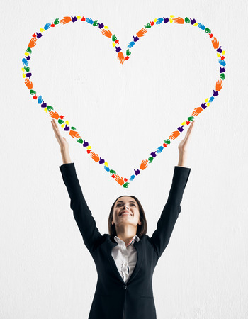 Young businesswoman holding creative hand gesture heart on white background. Community, charity and communication concept Stockfoto