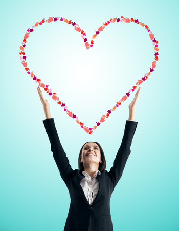 Young businesswoman holding creative hand gesture heart on blue background. Community, charity and communication concept