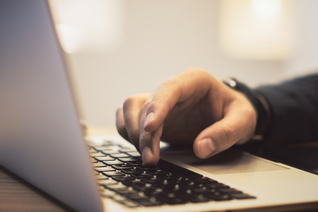 Side view of man hands using notebook keyboard on wooden desk top workplace. Blurry background. Education, communication, programming and software concept