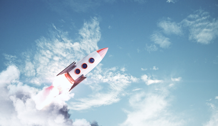 Creative launching rocket on bright blue sky with clouds background. Startup and entrepreneurship concept. 3D Rendering