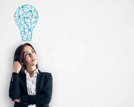 Jeune femme réfléchie avec croquis d'ampoule sur fond subtil. Idée, innovation, inspiration et concept de solution