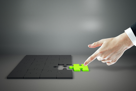 Businessman hand assembling green jigsaw puzzle on grey background. Quiz and solution concept 스톡 콘텐츠
